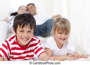 Brother and sister lying on floor in living-room