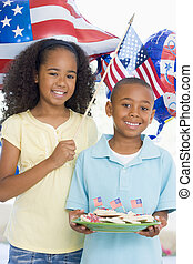 Brother and sister on fourth of July with flag and cookies...