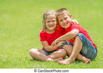 Brother and sister on lawn hugging.