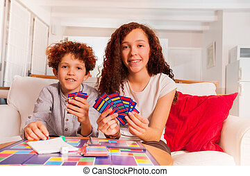 Brother and sister playing card games indoors