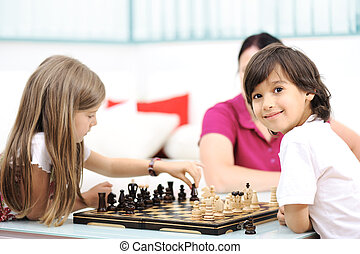 Brother and sister playing chess at home with their mother