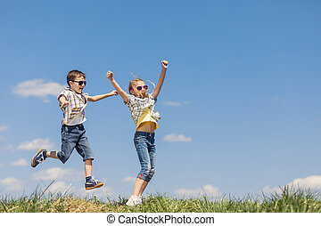 Brother and sister playing on the field at the day time.