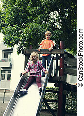 brother and sister playing on the playground