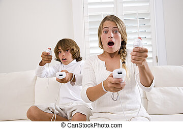 Brother and sister playing video game on white sofa