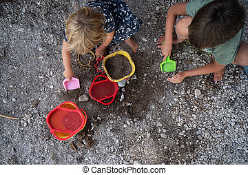 Brother and sister playing with pebbles, dirt and sand toys