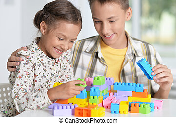 Brother and sister playing with plastic blocks