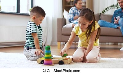 brother and sister playing with toy blocks at home
