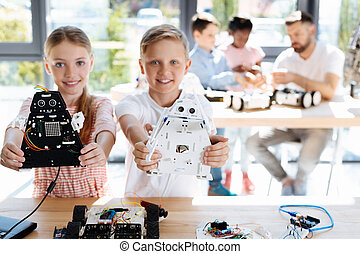Brother and sister posing with robot models
