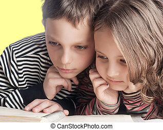 brother and sister reading a book, on the bed