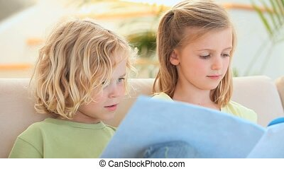 Brother and sister reading a story in the living room