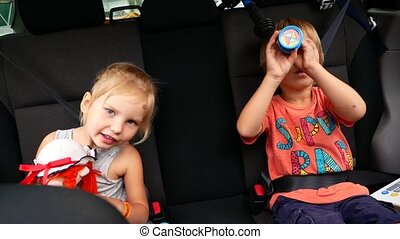Brother and sister ride in the back seat of the car without car seats