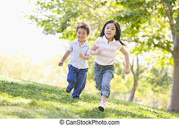 Brother and sister running outdoors smiling
