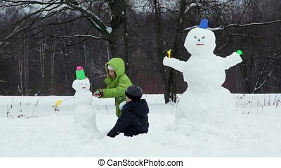 Brother and sister sculpt snowman in park at winter