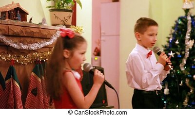 Brother and sister sing song into microphone