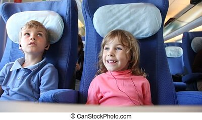 Brother and sister sit on places in train listen to music -...