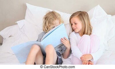 Brother and sister sit together on the bed and read a book