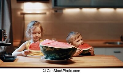 Brother and sister sitting at the table on kitchen. Boy and girl eating watermelon, enjoying the fruit.