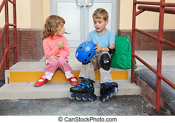 Brother and sister sitting on steps of house. Boy in roller skates, elbow and knee caps. In hands holding helmet.