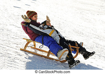 Brother and sister sledding down the hill, snow, winter, happiness and togetherness