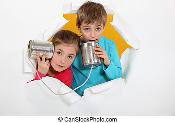 Brother and sister speaking into tin can