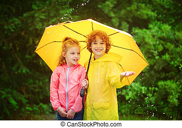 Brother and sister stand together under a big yellow umbrella.
