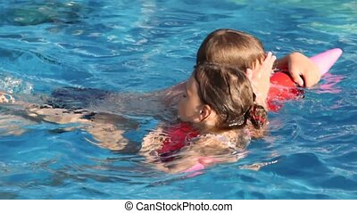 brother and sister swim on inflatable toy-pencil in pool