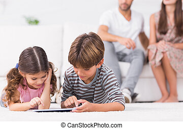 Brother and sister using tablet pc together on floor with...