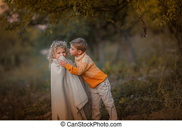 Brother and sister walking in the evening in the garden. The brother carefully covered his sister with a blanket