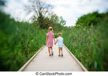 Brother and sister walking on the wooden platform