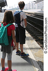 brother and sister with backpacks waiting for the train -...
