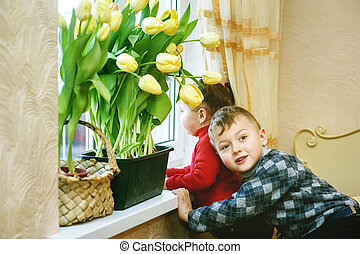 Brother and sister with flowers . Tulips in the window