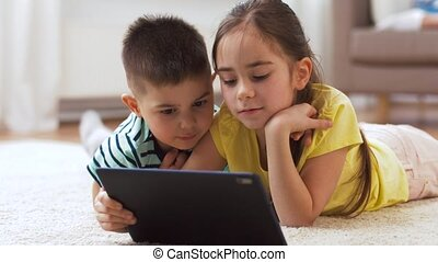 brother and sister with tablet computer at home - childhood,...