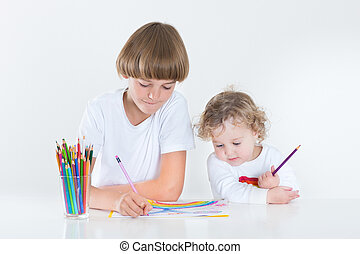 Brother and toddler sister paiting together in a white room at a