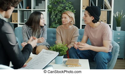Brother is fighting with sister in psychologist's office while mother is listening and commenting on fight between siblings. Emotions and family concept.