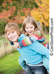 Brother giving sister piggy back - Older brother giving his...