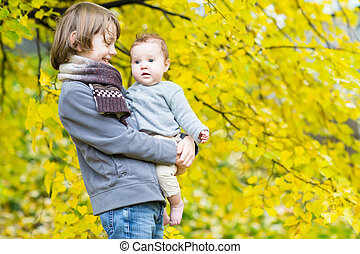 Brother holding his baby sister in a yellow autumn park