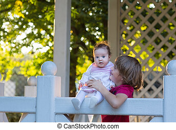 Brother holding his baby sister on a white wooden deck