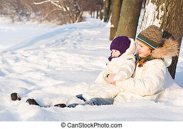 Brother holding his baby sister, playing in the snow
