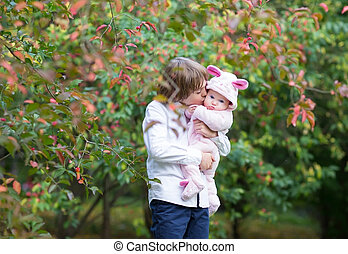 Brother kissing his baby sister under a colorful autumn tree