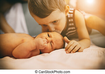 Brother kissing little newborn sister
