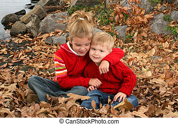 Brother Sister Hugging - Brother and sister sitting in fall...