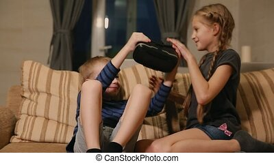 Brother with sister at home sitting on the couch playing the game using virtual reality glasses. Happy family
