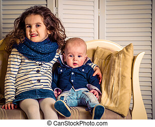 brother with sister on a beautiful sofa cushions