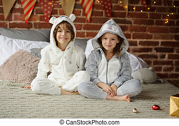 Brother with sister sit on a bed and expect Christmas gifts.