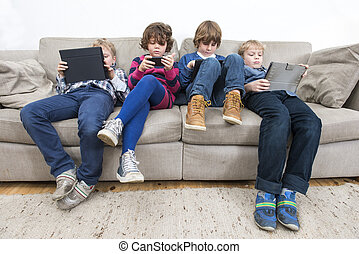 Brothers And Sister Using Technologies On Sofa - Brothers...