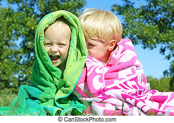 Brothers Giggling Wrapped in Beach Towels - Two happy young...