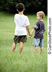 Brothers hold hands in field