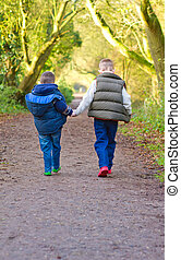 brothers holding hands on a countryside path