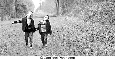 brothers holding hands together on a country path