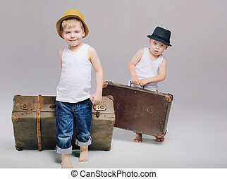 Brothers holding their heavy luggage - Brothers holding...
